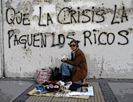 "A street vendor sits in front a wall that reads ""That the crisis pay the rich"", in downtown Santiago"